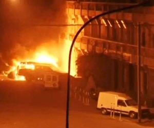 View shows vehicles on fire outside Splendid Hotel in Ouagadougou