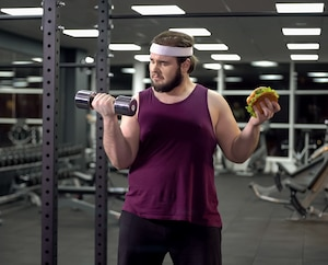 Obese male choosing between sport and fast food, burger addiction and motivation