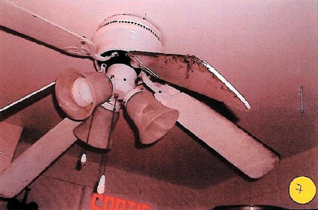 L'hélice d'un ventilateur plafonnier situé au-dessus de l'aire de plonge est couverte de poussière.