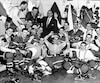 Cette photo témoigne bien de l'esprit de famille qui régnait chez le Canadien dans les années 1950, lorsque la formation a établi un record de cinq conquêtes d'affilée de la coupe Stanley. On peut voir, sur la première rangée : 10. Dickie Moore ; 11. Claude Provost ; 12. Floyd Curry ; 13. Bert Olmstead ; 14. Jacques Plante ; 15. André Pronovost ; 16. Bob Turner ; 17. Marcel Bonin ; 18. Phil Goyette. Sur la deuxième rangée, on aperçoit : 1. Doug Harvey ; 9. Dollard Saint-Laurent ; 2. Henri Richard ; 3. Toe Blake (entraîneur) ; 4. Tom Johnson ; 5. Bernard Geoffrion ; 6. Jean Béliveau ; 7. Don Marshall ; 8. Maurice Richard.
