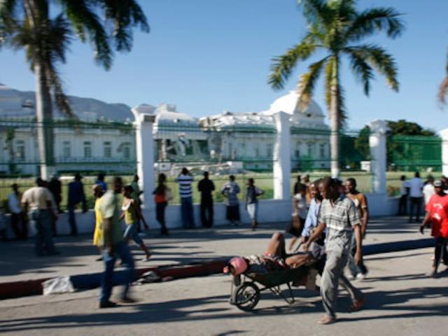 PORT-AU-PRINCE  Les gens utilisaient des brouettes pour transporter les blessés dans les rues de la Capitale. On aperçoit le Palais présidentiel qui a été lourdement endommagé.