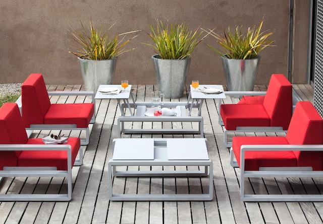 Dans la catégorie haut de gamme, la table modulable Kama du manufacturier français EGO-Paris, montrée ici avec les fauteuils Club de la même collection, offre un design épuré très contemporain. Elle est constituée de deux plateaux munis d'un mécanisme permettant d'en régler la hauteur. On peut ainsi l'utiliser comme table à café ou comme table à manger. Structure en aluminium laqué (22 coloris). Plateaux en Corian blanc, céramique ou aluminium givré (9 coloris).