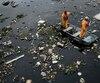 Des employés s'affairent à capter des débris se dirigeant vers la baie de Guanabara.