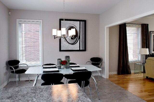 Pivot du rez-de-chaussée, la salle à manger est aussi magnifiquement éclairée de lumière naturelle, grâce à sa fenêtre de côté et ses portes-fenêtres coulissantes qui s'ouvrent sur la terrasse en béton, côté cour.
