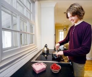 Christophe Bettez-Théroux en train de se préparer un dessert avec des framboises, l'un de ses fruits préférés.
