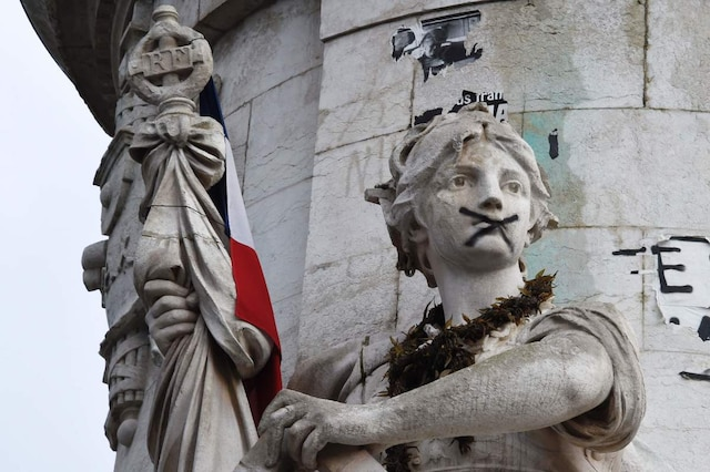 A sculpture with an 'X' sprayed across her mouth decorates the base of the statue of Marianne at Place de la Republique (Republic square) where a remembrance rally was held on January 10, 2016 to mark a year since 1.6 million people thronged the French capital in a show of unity after attacks on the Charlie Hebdo newspaper and a Jewish supermarket.  Just as it was last year, the vast Place de la Republique will be the focus of the gathering as people reiterate their support for freedom of expression and remember the other victims of what would become a year of jihadist outrages in France, culminating in the November 13 coordinated shootings and suicide bombings that killed 130 people and were claimed by the Islamic State (IS) group.  / AFP / DOMINIQUE FAGET