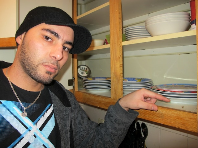 Fehd Chemek montre une coquerelle morte trouvée hier, dans une armoire de cuisine, où il range ses assiettes.