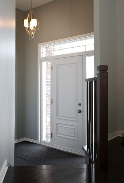 Le hall d'entrée en céramique, sous un plafond de 12 pieds, combine porte d'accès au garage, placard et demi-escalier vers le sous-sol.