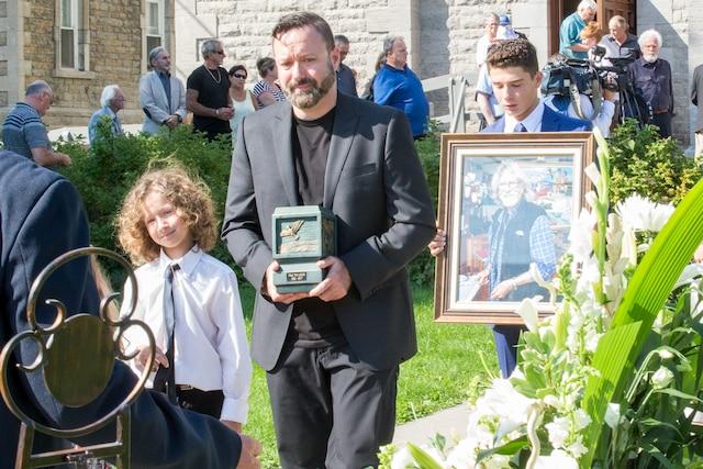 Sur la photo de gauche, un membre de la famille transporte les cendres du réputé personnage.