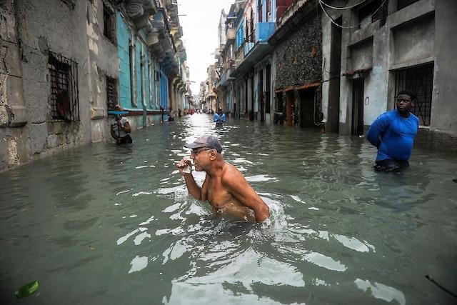 Un homme marche dans une rue inondée de La Havane.