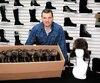 Le copropriétaire de Bilodeau Canada, Mario Bilodeau, pose dans les ateliers de l'entreprise avec quelques chapeaux de la GRC.