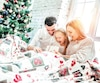 Family hugging near christmas tree on the bed. New year's morning