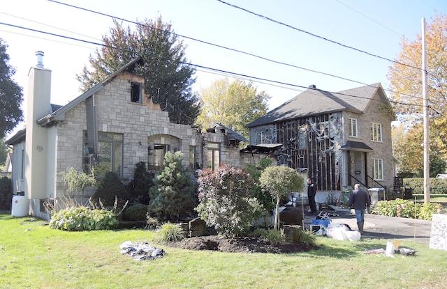 Le feu qui s'est déclaré dans la résidence des parents de l'homme qui semble être visé (à gauche sur la photo) s'est propagé jusque chez son voisin.
