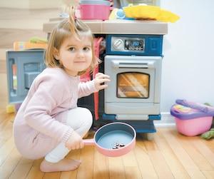 Ève Lemay, 3 ans, s'amuse avec sa mini-cuisinière pour enfant, elle qui a reçu un diagnostic de 12allergies alimentaires à sept mois.