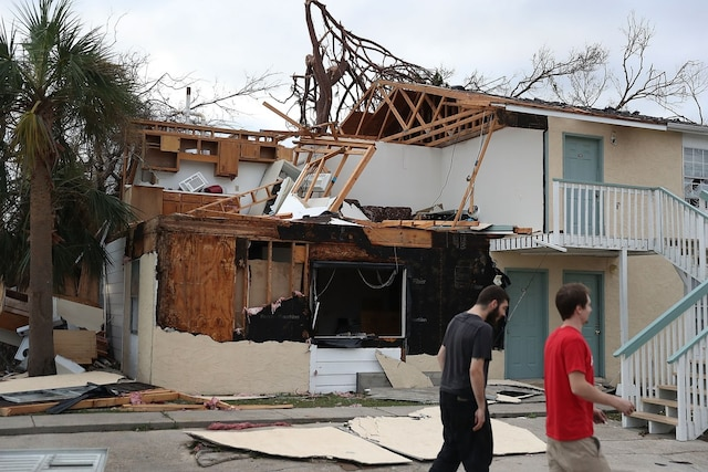 PANAMA CITY, FL - OCTOBER 11: People walk past an apartment destroyed by Hurricane Michael on October 11, 2018 in Panama City, Florida. The hurricane hit the Florida Panhandle as a category 4 storm.   Joe Raedle/Getty Images/AFP == FOR NEWSPAPERS, INTERNET, TELCOS & TELEVISION USE ONLY ==