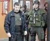 Le tueur à gages devenu délateur Gérald Gallant, que l'on voit ici en2009 protégé par une veste pare-balles et surveillé par des policiers armés, sur les lieux de son dernier meurtre commis au commerce de son complice Raymond Bouchard.