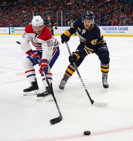 BUFFALO, NY - MARCH 23: Artturi Lehkonen #62 of the Montreal Canadiens and Brendan Guhle #45 of the Buffalo Sabres go after a loose puck during the third period at KeyBank Center on March 23, 2018 in Buffalo, New York.   Kevin Hoffman/Getty Images/AFP == FOR NEWSPAPERS, INTERNET, TELCOS & TELEVISION USE ONLY ==