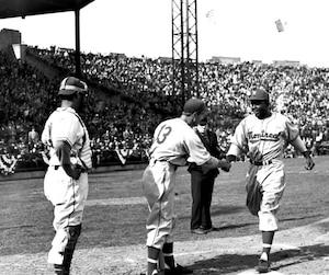 Jackie Robinson savait se distinguer lors des grandes occasions. À son tout premier match dans le « baseball blanc », le 18 avril 1946 au Roosevelt Stadium de Jersey City, il frappe quatre coups sûrs, dont un circuit, en cinq présences au bâton dans une victoire de 14 à 1 des Royaux. Il marque quatre points, en produit autant, en plus de voler deux buts. Son coéquipier George Shuba le félicite alors qu'il croise le marbre après son circuit.