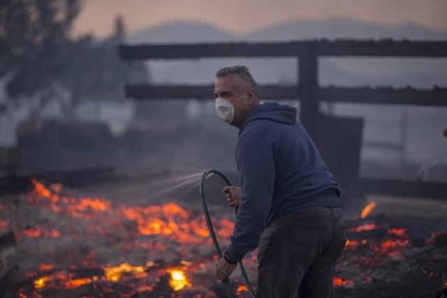 Un résident dirige un tuyau d'arrosage vers sa maison en flammes à Sunland, en Californie.