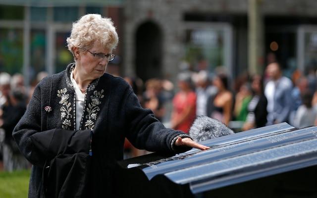 Une femme regarde le monument en hommage aux victimes de la tragédie de Lac-Mégantic, à la suite de la messe commémorative à l'église Sainte-Agnès, le 6 juillet 2014.