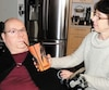 Alain Gaudet reçoit de l'eau de son employée Monique Martel, qui vient le sortir du lit les matins, chez lui, à Trois-Rivières.