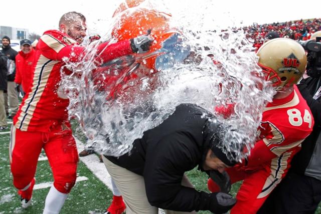L'entraîneur chef du Rouge et Or de l'Université Laval, Glen Constantin, se fait arroser par des membres de son équipe après avoir gagné la Coupe Vanier.