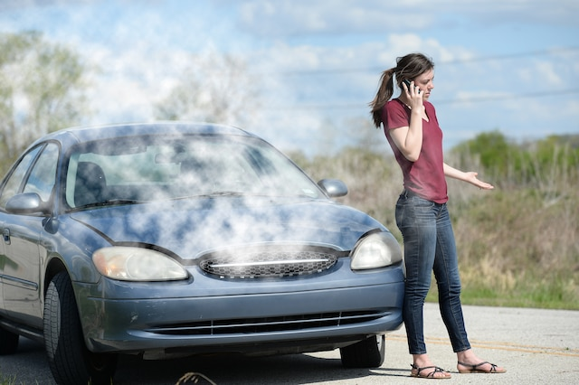 A teenage girl is broken down on the side of the road after car began to overheat