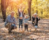 Grandparents and grandchildren throwing leaves in park and having fun together