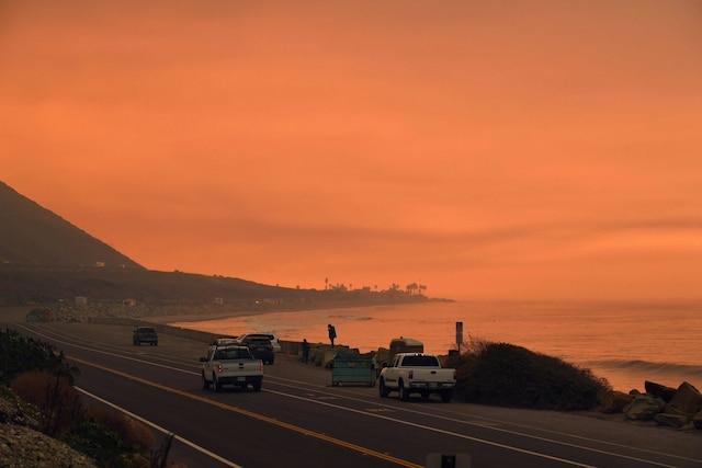 Une épaisse fumée recouvre la Pacific Coast Highway, au moment où des flammes se rapprochent des côtes pendant le feu de forêt Thomas, près de Ventura, en California. Des automobilistes californiens ont conduit à travers un brasier infernal mercredi, alors que des feux de forêt fouettés par le vent faisaient rage dans la région de Los Angeles, les flammes entraînant la fermeture de cette autoroute majeure.
