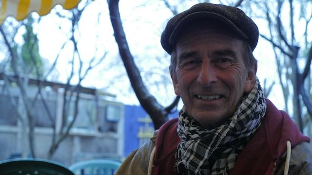 Garth Gilker, fondateur du café Santropol, assis à l'entrée de sa terrasse intérieure.