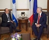 Hollande speaks with Couillard during a meeting in Quebec City