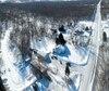 Sur cette photo aérienne apparaît au centre la petite maison blanche de Réal Croteau. Les carcasses de véhicules s'accumulent sous la neige et entre les arbres chez les voisins des deux côtés et en arrière de sa propriété.