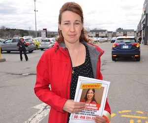 Annie Major, la sœur de Karine Major, alors qu'elle tapissait la ville de Rimouski d'affiches pour retrouver sa sœur le 11 mai dernier.