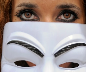 A protester wears a Guy Fawkes mask as she participates in a demonstration against the ACTA in Brussels