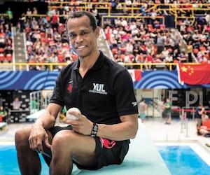 Une balle de baseball à la main est devenue la marque de commerce de César Henderson, un entraîneur de plongeon originaire de la République dominicaine qui forme des champions au Québec depuis plus de 30 ans.