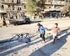 Boys run near a hole in the ground after airstrikes by pro-Syrian government forces in the rebel held al-Sakhour neighborhood of Aleppo