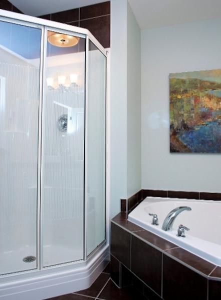 La salle de bains en céramique, avec un grand bain en coin et une confortable douche vitrée, est dotée d'une spacieuse vanité, avec lavabo surélevé très design.