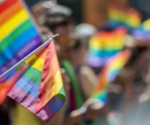 GayPride spectators carrying Rainbow gay flags during Montreal Pride March in 2015