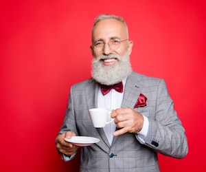 Portrait of cool, manly, elegant, fashionable man looking at camera, having mug with tea and saucer in arms, isolated on red background