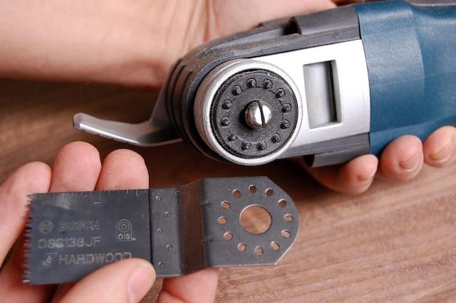 Le système de changement de lame n'exige aucun outil et comporte un levier sur le côté de l'outil qu'il suffit de déplacer afin de dégager la lame. Le pivot central, qui est fendu en deux, s'élargit pour immobiliser solidement la lame. Les petites tiges disposées au périmètre permettent de bloquer la lame à différents angles.
