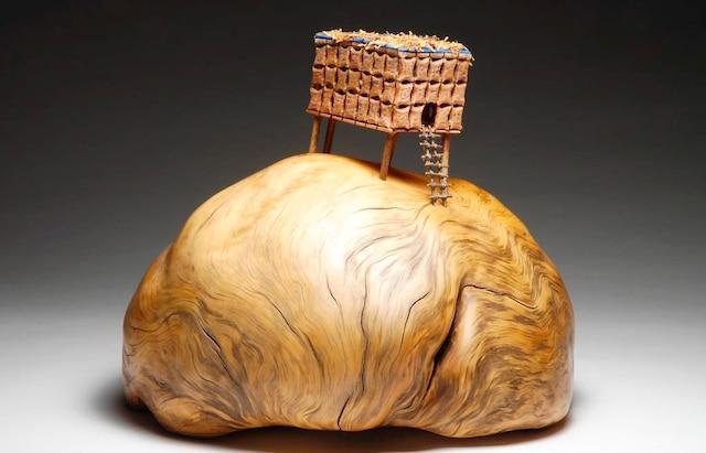 <b><i>Ceci est l'œuvre d'artistes contemporains– 2015</i><br /> Loupe de pin rouge, bois, métal, acrylique, mousse de tourbe.<br /> 20cm x 17cm x 18cm</b><br /> Une maison de fortune instable, construite en sacs de riz par Kim et sa famille pour tenter de survivre.