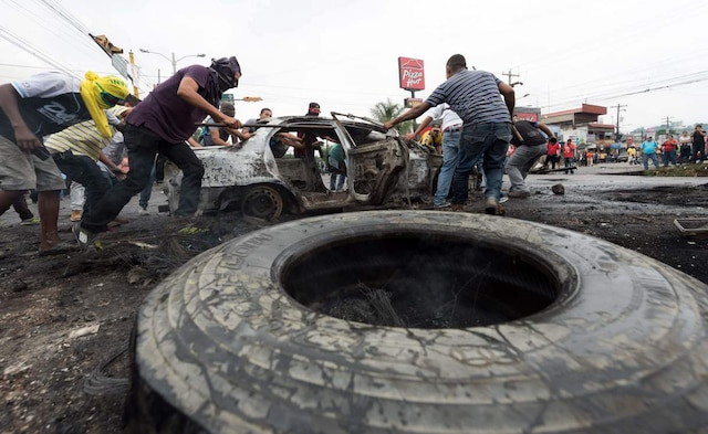 Supporters of Honduran presidential candidate for the Opposition Alliance against the Dictatorship coalition Salvador Nasralla move a car burnt during protests demanding the final results of the weekend's presidential election, in Tegucigalpa, on December 1, 2017.   Fresh clashes broke out Friday between riot police and opposition supporters in Honduras, as the counting of votes in a cliff-hanging presidential election rolled into a fifth day. Police said at least 12 civilians were injured, some by gunfire, after violence erupted in several parts of the country -- sparked by opposition candidate Salvador Nasralla claiming fraud and calling his supporters onto the streets.   / AFP PHOTO / JORDAN PERDOMO