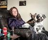 Stéphanie Guénette, ici dans son salon de Saint-Lin–Laurentides avec ses deux chiens, souffre de douleurs chroniques qui peuvent l'empêcher de marcher, de dormir et de se tourner.