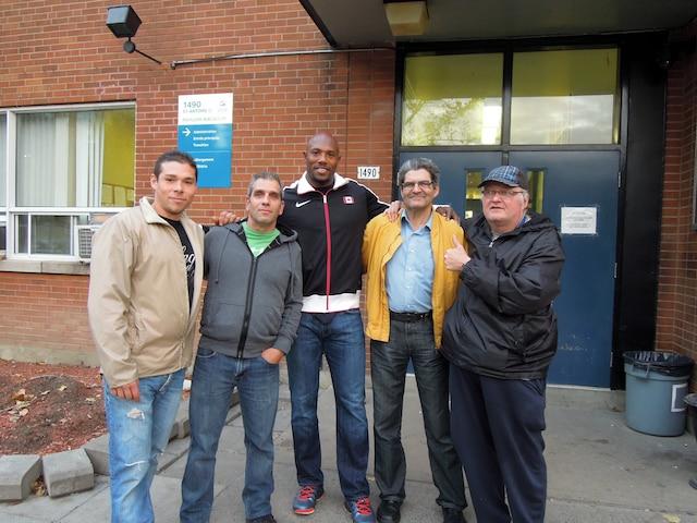 Kyrie Hebert prend la pose avec des résidents devant le refuge de la  Mission.