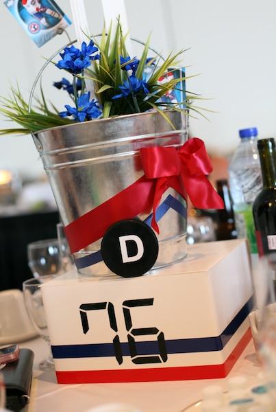 Les centres de tables étaient confectionnés avec des boîtes indiquant le numéro d'un joueur du Canadien, sa carte de hockey, des rubans et des fleurs bleu-blanc-rouge.