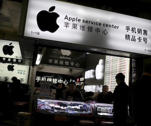 File photo of customers and salespersons at an Apple maintenance service store at a mobile phone market in Shanghai