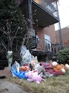 Les toutous et les fleurs continuent de s'accumuler au pied de l'escalier menant au lieu du drame.