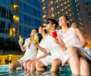 Chinese couples drinking cocktails in hotel pool bar