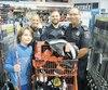 Charles-Antoine expose fièrement son nouvel équipement aux côtés des policiers de la Ville de Québec Mathieu Renaud, Audrey Boulet et Denis Couture.