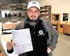 Le Montréalais Mike Skyllas a posé dans les locaux de son entreprise d'aménagement de salles de bain avec sa facture d'Hydro-Québec dont le montant s'élève à 2sous.